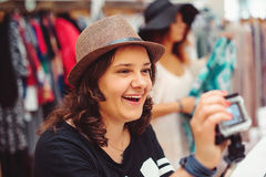 Smiling attractive young women in a hat shopping at clothes store. Shopping time. Summer sale. Smiling attractive young woman in  hat shopping at clothes store Royalty Free Stock Photo