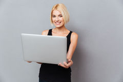 Smiling attrative young woman standing and using laptop Stock Images
