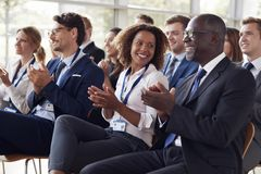 Smiling audience applauding at a business seminar royalty free stock photos