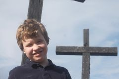 Smiling Autistic Boy in Front of a Cross Stock Photo