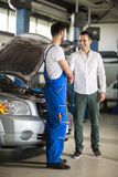 Smiling auto mechanic and client shaking hands. In sevice Stock Photo
