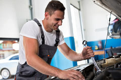 Smiling auto mechanic. Smiling mechanic repairing car in auto service Royalty Free Stock Photo