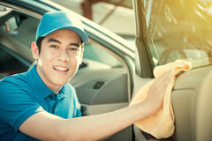 Smiling auto service staff cleaning car door Royalty Free Stock Photos
