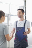 Smiling automobile mechanic shaking hands with female customer in automobile repair shop Stock Image