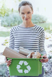 Smiling woman segregating paper junk. Smiling aware woman holding a green container with segregated paper junk. Segregating paper waste concept Royalty Free Stock Photography