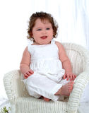 Smiling Baby. Baby girl sitting on wicker chair in front of white background Royalty Free Stock Images