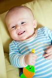 Smiling baby. With toy lying on sofa royalty free stock images