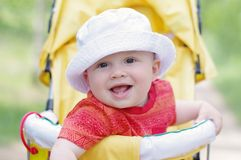Smiling baby age of 9 months on baby carriage. Smiling lovely baby age of 9 months on baby carriage Royalty Free Stock Photography