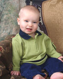 Smiling Baby on Antique Chair. Baby boy sitting in front of muslin background on old antique chair stock images
