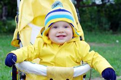 Smiling baby on baby carriage. Smiling baby on yellow baby carriage Royalty Free Stock Photos