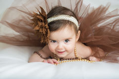 Smiling baby ballerina in brown tutu. With a pearl necklace Stock Photography