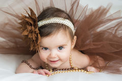 Smiling baby ballerina in brown tutu. With a pearl necklace Royalty Free Stock Image
