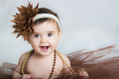 Smiling baby ballerina in brown tutu. With a pearl necklace Royalty Free Stock Photos
