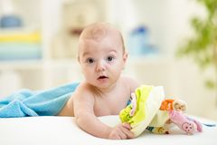 Smiling baby in a bathing towel with toy. Cute baby in a bathing towel with toy stock photo