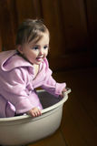 Smiling baby in a bathrobe sits in a basin Stock Photo