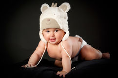 Smiling baby in bear cap. In black background Royalty Free Stock Photography