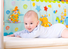 Smiling baby in bed royalty free stock photography