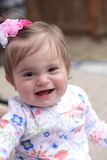 Smiling baby and a bow. A smiling happy 1 yr old baby girl with a pink bow in her dark hair smiling and having fun.  Shallow depth of field. Selective focus Stock Image