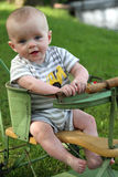Smiling baby boy in antique stroller waterside Royalty Free Stock Image