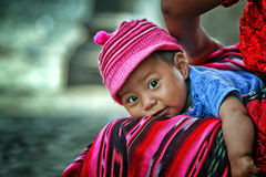 Smiling baby boy with big eyes laying down and looking at camera. Baby boy laying down on his mother's lap in the colonial city of Antigua, Guatemala. Taken royalty free stock image