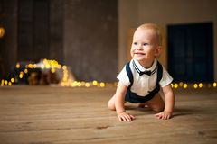 Smiling baby boy crawls against background of garland of glowing light bulbs. Smiling baby boy crawls at the floor against background of garland of glowing light stock image