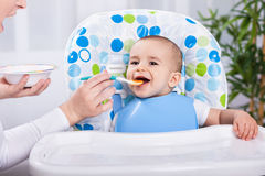 Smiling baby boy enjoy at feeding time. In kitchen Royalty Free Stock Images
