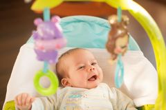 A smiling baby boy lieing in the swinger and looking at the toys stock photo