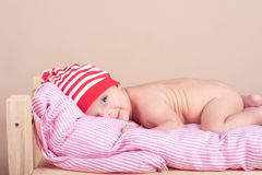 Smiling baby boy lying in bed on beige Stock Images