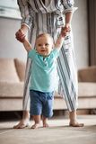 Smiling baby boy making first steps with mother stock images