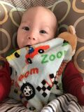 Smiling baby boy with blanket. Smiling baby boy playing with blanket; smile reaches his eyes, and blanket is being pulled up over his chin Royalty Free Stock Photos