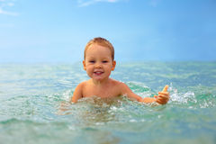 Smiling baby boy playing with sea water Stock Image