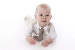 Smiling baby-boy in a romper suit crawling. Smiling baby in a beige romper suit and tie crawling. On a white background with reflection Royalty Free Stock Photos