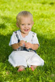 Smiling baby boy sits in the summer park Royalty Free Stock Photo