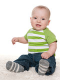 Smiling baby boy sits on the white carpet Stock Image