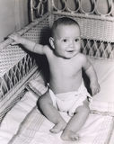 Smiling baby boy sitting in crib Stock Photo