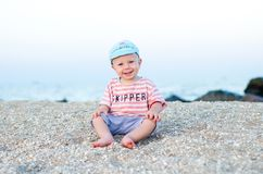 Smiling baby boy sitting on the sand  near sea. Summer concept. Holiday relaxing, beach. Vacation Stock Photo