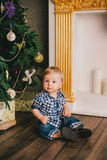 Smiling baby-boy sitting under Chritmas tree near fireplace Royalty Free Stock Images