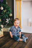 Smiling baby-boy sitting under Chritmas tree near fireplace Royalty Free Stock Photography