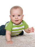 Smiling baby boy on the white carpet Royalty Free Stock Images