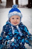 Smiling baby boy in winter snow Stock Image