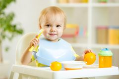 Smiling baby child boy eating itself with spoon. Smiling cute child baby boy eating itself with spoon stock images