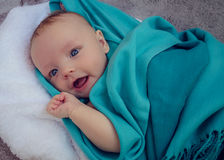 Smiling baby covered in blue blanket Royalty Free Stock Images
