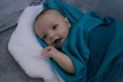Smiling baby covered in blue blanket Royalty Free Stock Photo