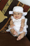 Smiling Baby in Dress. Happy, smiling baby girl with blue eyes in a fancy white dress sitting on a chair laughing stock photos