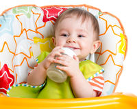 Smiling baby drinking milk from bottle Royalty Free Stock Photos