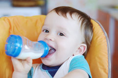 Smiling baby drinks milk from a small bottle Stock Images