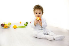 Smiling baby eating banana and many kinds of fruit and bowl with yoghurt Royalty Free Stock Photos