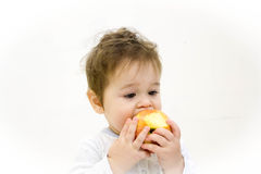 Smiling baby eating banana and many kinds of fruit and bowl with yoghurt Royalty Free Stock Image