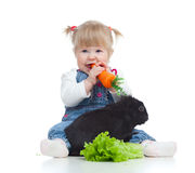 Smiling baby eating a carrot and feeding rabbit Stock Photo