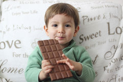 Smiling baby eating a chocolate tablet Royalty Free Stock Images